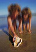 PHOTO : Deux enfants trouvant un strombe sur la plage.